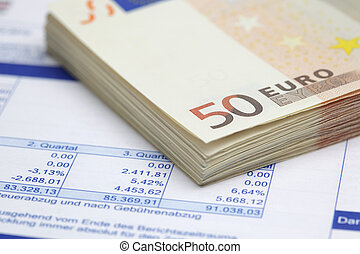 Financial figures - Stack of Euro bills on financial report