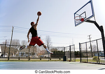 Man Dunking the Basketball - A young basketball player...