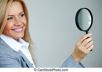 business woman looking through a magnifying glass