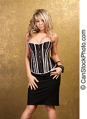 sexy blonde woman in corset and skirt on golden background