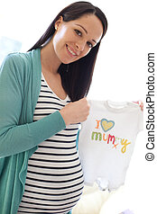 pregnancy - Portrait of a happy young pregnant woman holding...