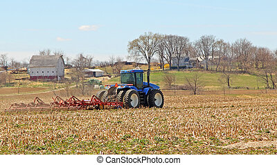 Tractor and Plow - Blue farm tractor plowing a farm field