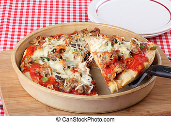 Deep Dish Pizza Slice - Sausage and mushroom pizza in a deep...