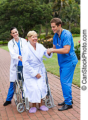 nurse helping senior patient get up - young caring doctor...