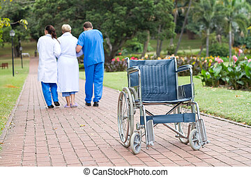 get up from wheelchair - caring doctor and nurse helping...