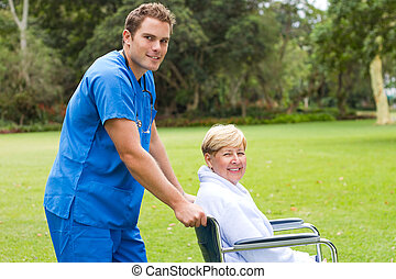 male nurse and senior patient - male nurse pushing a senior...