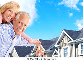 seniors - Smiling happy elderly seniors couple near the home...
