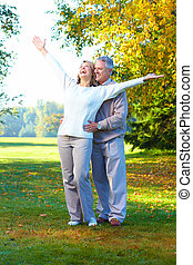 lderly seniors couple - Happy elderly seniors couple in park...