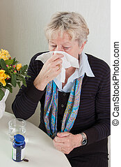 Elderly woman with the flu or bad cold. She is blowing her...