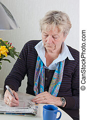 senior crossword puzzle - senior woman is doing the...