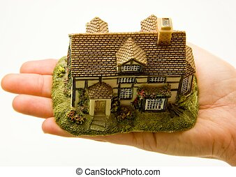 Hand holding minature of house - Female hand on white...