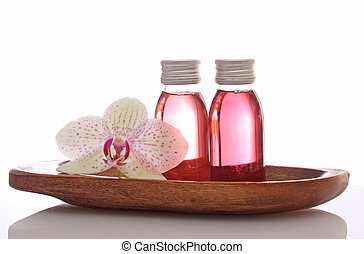 bottles with essential oils and orchid in bowl isolated on...