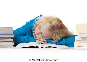 Pretty young blond schoolgirl sleeps on schoolbook.Isolated...