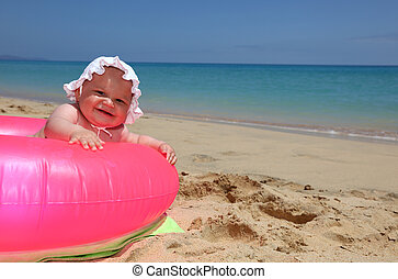 Happy baby in a pink ring on tropical beach