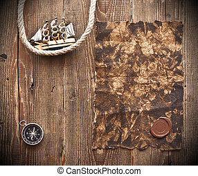 old paper, rope and model classic boat on wood background