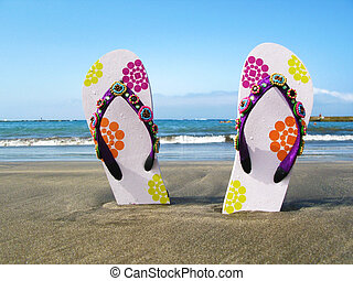Flip-flops in the black volcanic sand of Tenerife island,...