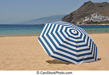 Striped umbrella on the Teresitas beach of Tenerife island....