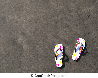 Flip-flops and hat on the black sand of Tenerife island,...