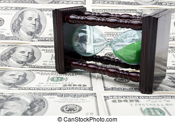 hourglass and money with dolars as a background