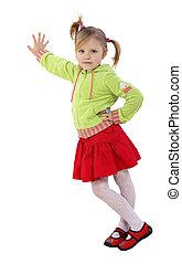 little girl stands near a wall, red skirt, green womans...