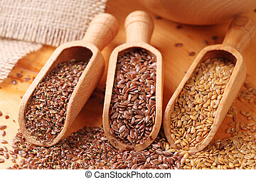 Flax seeds - Wood spoons with whole brown, golden and ground...