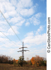 Electric tower poles on the yellow meadow over sky