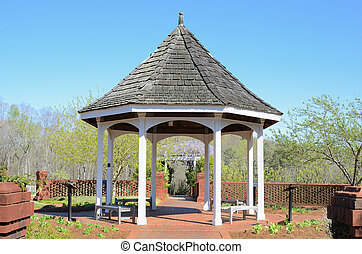 Gazebo - A gazebo surrounded by a brick wall in a little...
