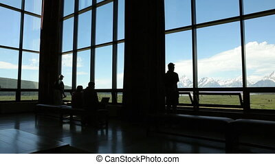 Grand Tetons from lodge - Silhouette of tourists viewing the...