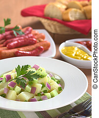 Fresh potato salad with cucumber, red and green onion made with an oil dressing with barbecued sausages, mustard, ketchup and baguette in the back (Selective Focus, Focus on the front of the salad and