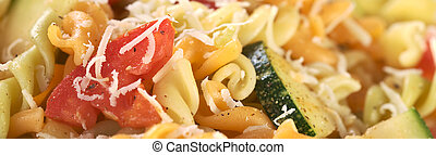 Colorful fusilli pasta with zucchini, tomato and grated cheese (Selective Focus, Focus on the outer side of the tomato)