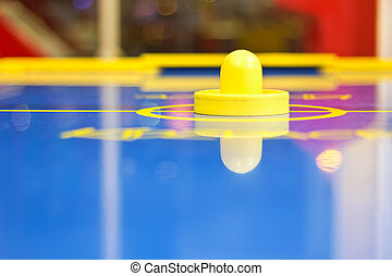 Yellow air hockey mallet on a blue an air-hockey table