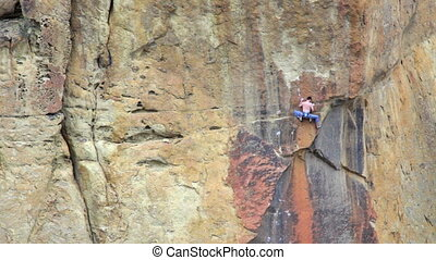 Rock Climber - Man rock climbing and making a big jump for...