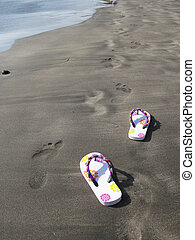 Flip-flops on the black sand of Tenerife island, Canaries