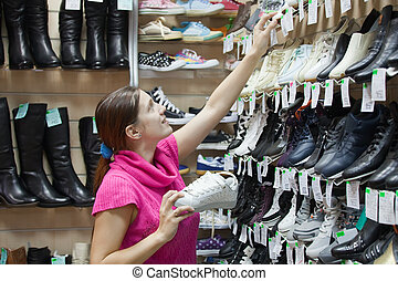 girl chooses shoes at shoes shop