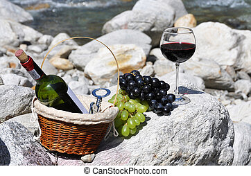 Red wine and grapes served at a picnic. Verzasca valley,...