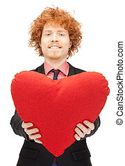 handsome man with red heart-shaped pillow - picture of...