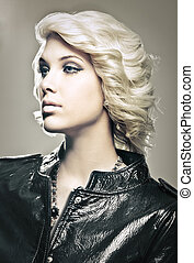 Beautiful young blond fashion model with leather jacket...