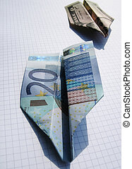 Two paper airplanes made of euro and dollar notes