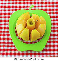 Apple - Yellow apple cut by a green tool over white and red...