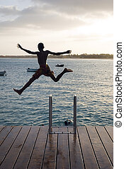 silhouette of boy jumping off pier. - A color portrait photo...