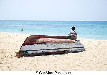 man sitting on an upturned boat