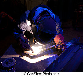 Dramatic TIG welding close up - Blue-lit TIG welder working...