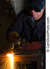 Close up of welder with orange sparks - Welder uses torch to...