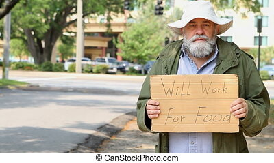 Homeless Man - Homeless man stands at the side of the road...