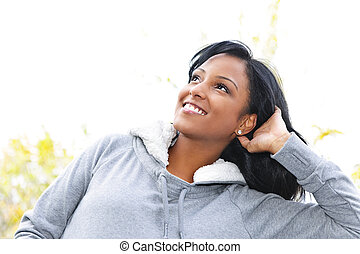 Smiling young woman outdoors looking up - Portrait of happy...