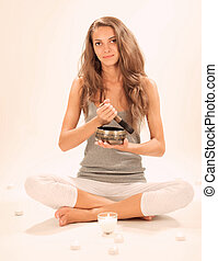 Young beautiful lady relaxing with nepal singing bowl and...