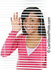 Smiling woman looking through blinds - Happy young black...