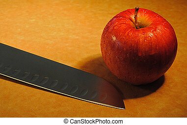 Apple and Knife - An apple and a knife on a cutting board.