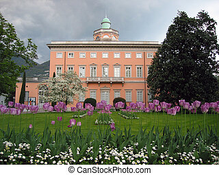 Classical mansion and lilac tulips in foreground. Lugano,...