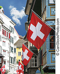 Old street in Zurich decorated with flags for the Swiss National Day